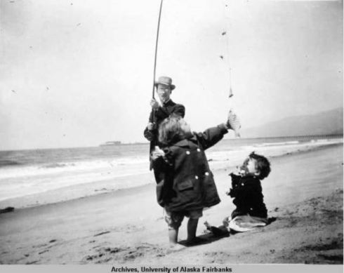 Man_and_two_children_on_beach_with_fishing_pole.jpg